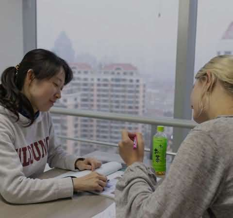 Chinese teacher is helping her student, explaining what is written in her Chinese book
