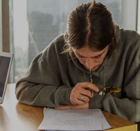 A student studying in a classroom and biting his pen as he looks at his paper.  Learning Chinese is easy and not easy!
