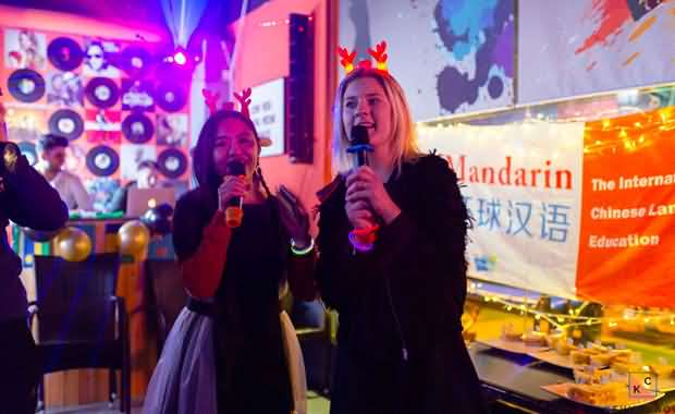 Two beautiful hosts with microphones in Boky's Bar at the XMandarin Xmas party