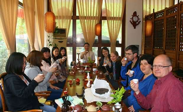 10 students holding their teacups enjoying a Chinese tea party in Qingdao