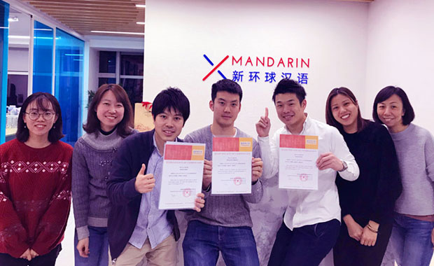 Three Japanese students are happy with graduation certificates and their Chinese teachers in front of the XMandarin logo wall