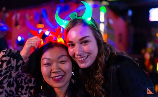 Two smiling cute girls wearing green and red glowing hairbands at the 2018 XMandarin Xmas party