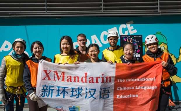 Group of international Chinese language students, chinese teachers, and our service team, holding the XMandarin flag during a rock climbing event