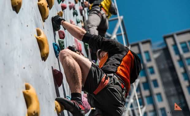 An XMandarin student climbing a wall during an event, outside in Qingdao with good weather and blue sky