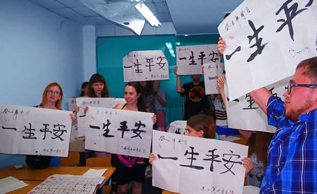"Group of XMandarin students holding their Chinese calligraphy (一生平安 ""long and peaceful life"") art during an extra-curricular event"